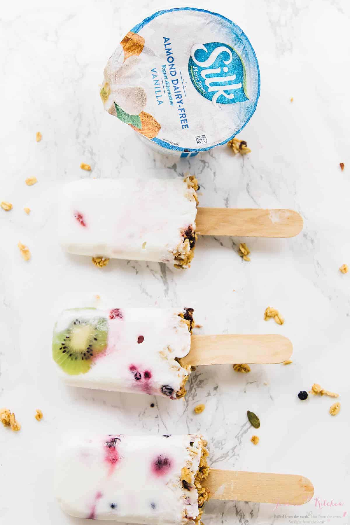 Top down shot of parfait popsicles on a white table next to a pot of yogurt.