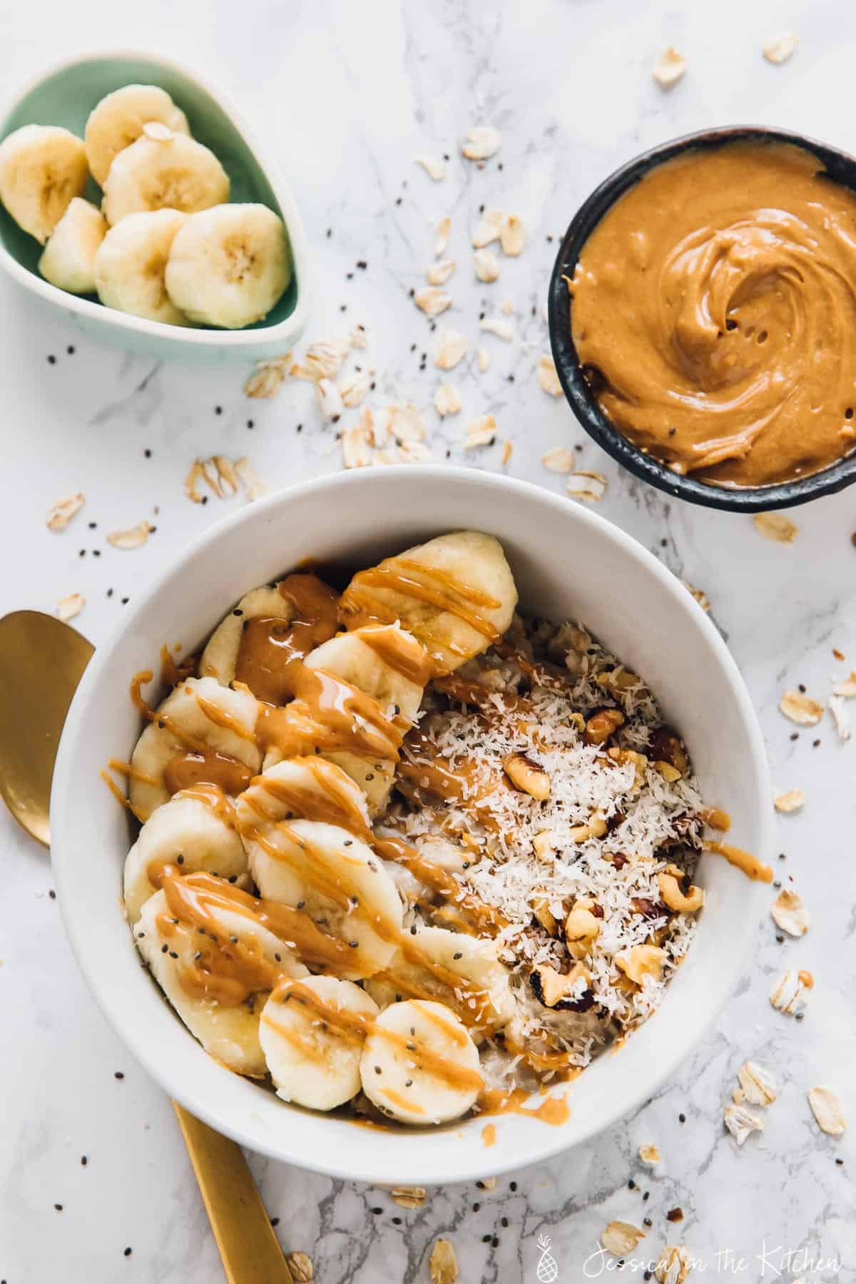Overhead view of oats in a bowl with slices bananas and peanut butter drizzled on top.