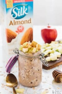 Apple cinnamon overnight oats in a glass jar, topped with diced apples.