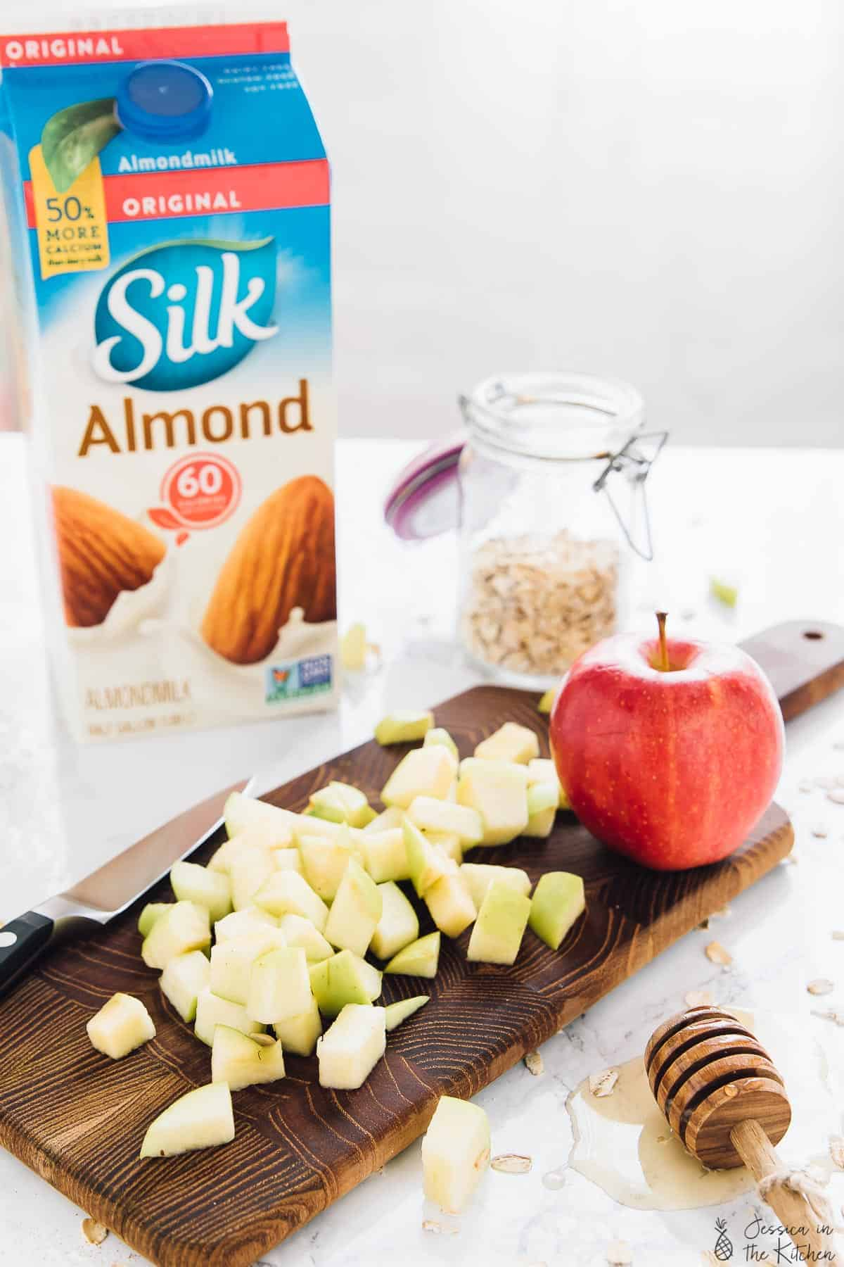 Diced apples on a wood board with a carton of almond milk in the background.