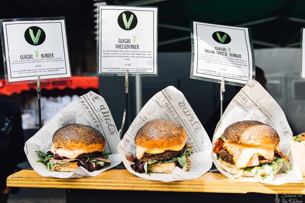 Three burgers on a wood plank.