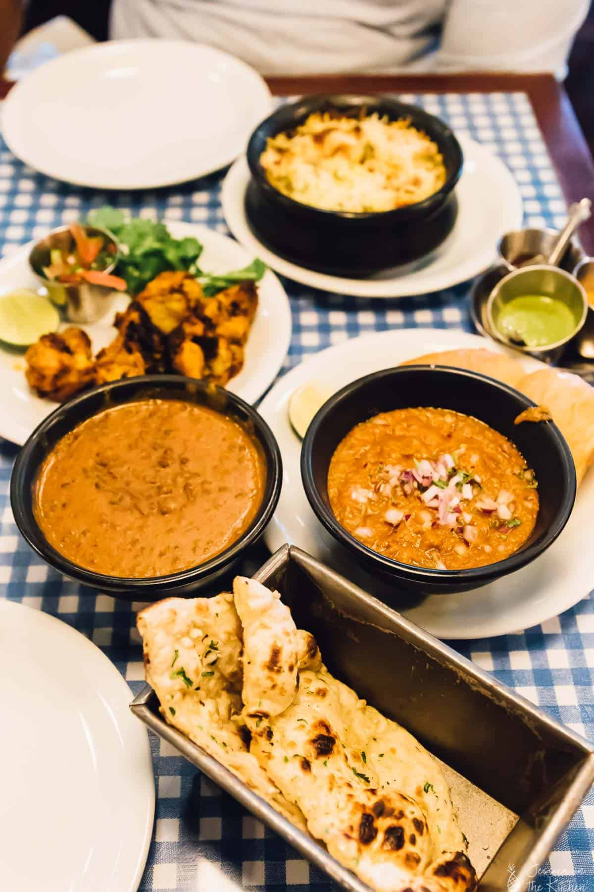 A table spread with bowls of curry and naan bread.