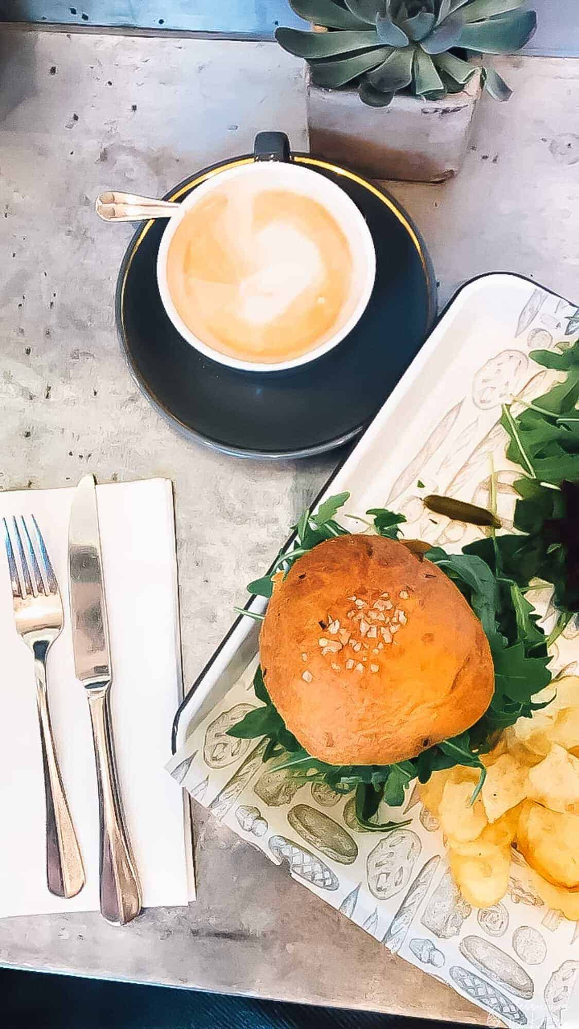 Top down view of a burger and coffee on a table.