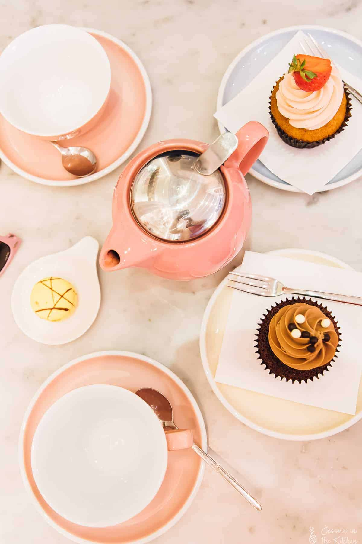 Top down view of pink cups and cupcakes on a table.