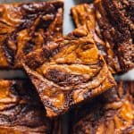 A top down view of a batch of vegan Pumpkin Cheesecake Swirl Brownies on a white table.