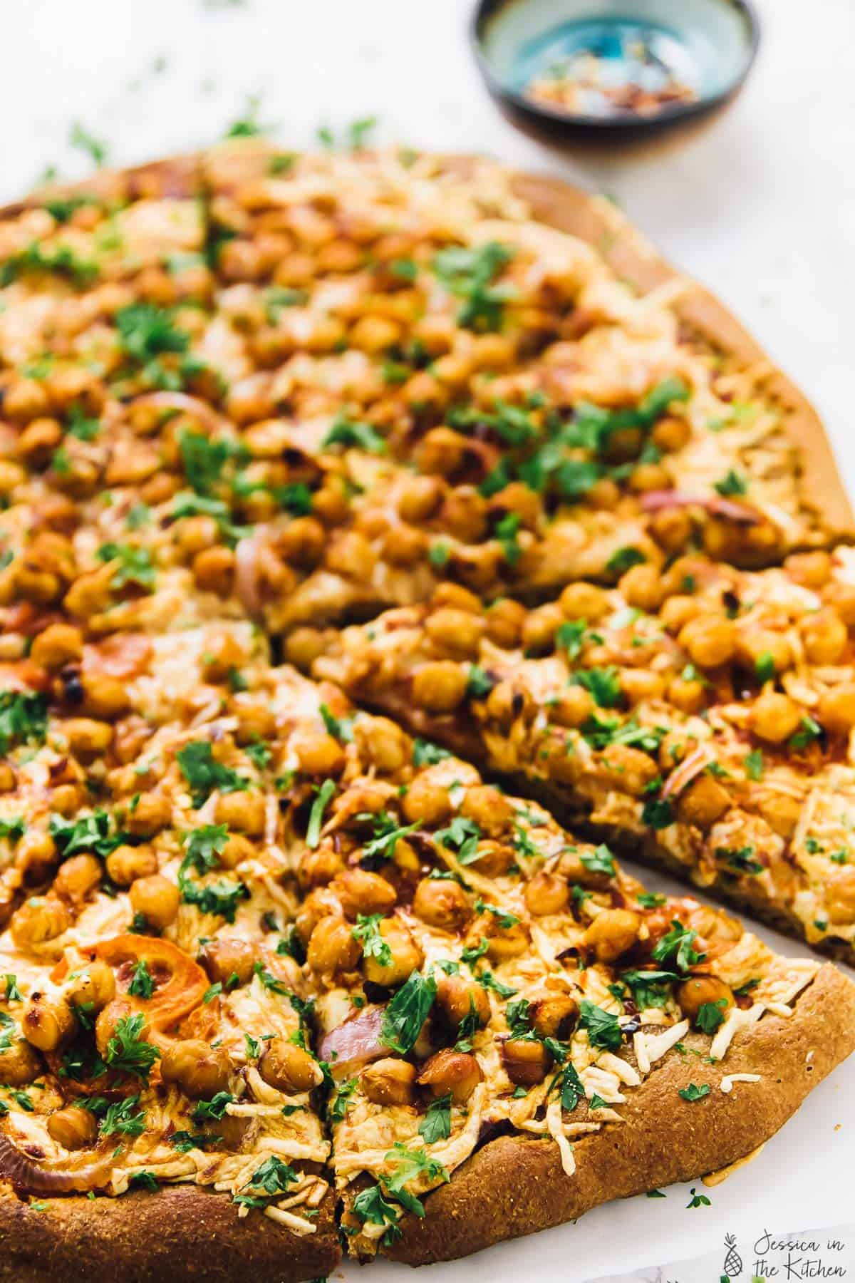 This Vegan Spicy BBQ Chickpea Pizza is a sweet and spicy pizza hit! It's so easy you can make it on a weeknight while adding extra protein to your meal! via https://jessicainthekitchen.com
