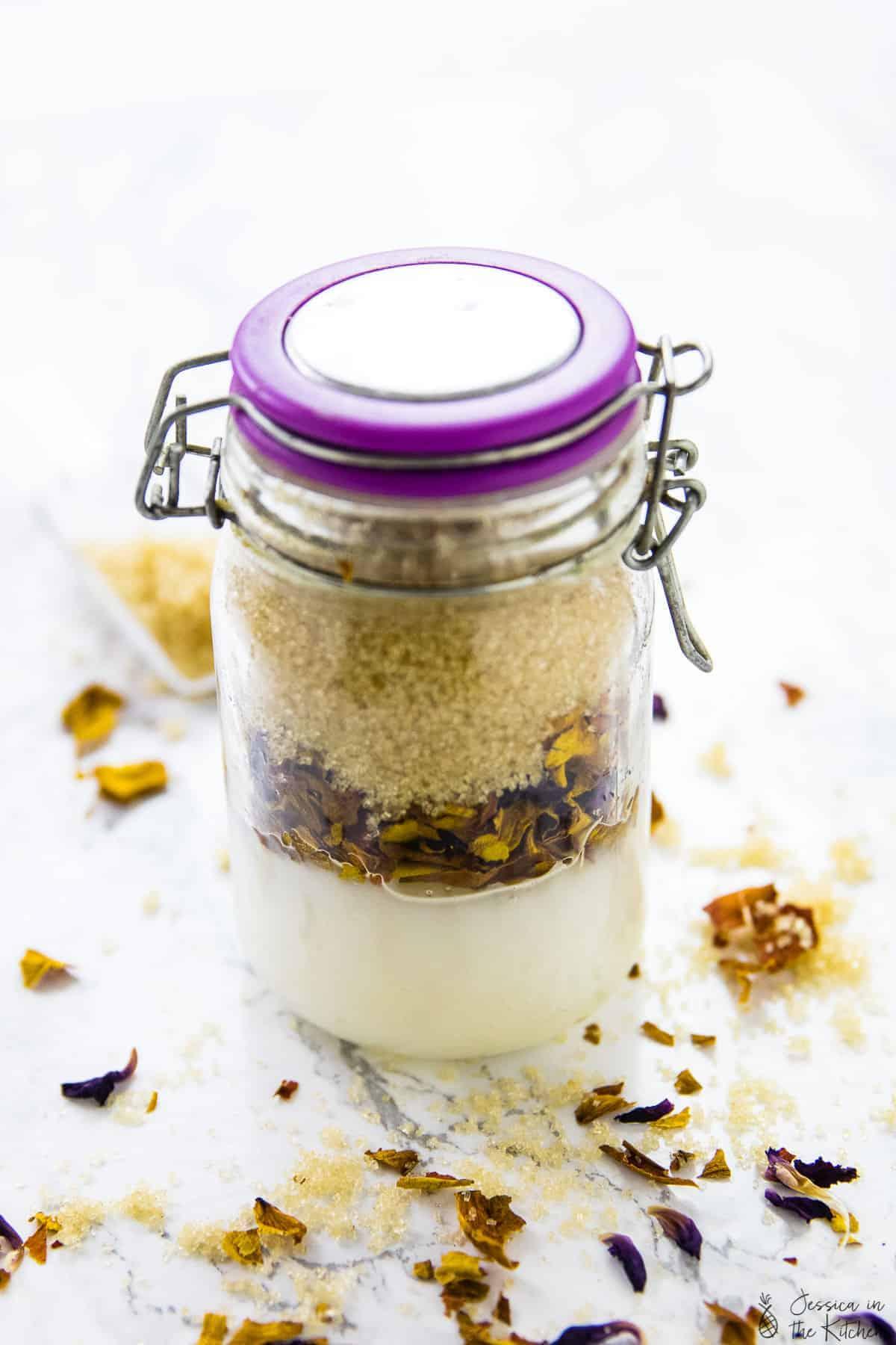 Coconut rose sugar scrub in a closed glass jar.