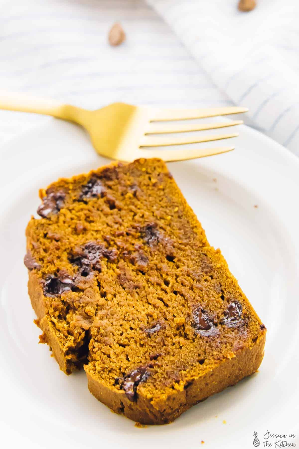 A slice of chocolate chip pumpkin bread on a plate with a gold fork on the side.