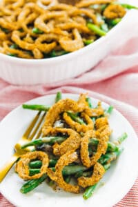 Green bean casserole on a plate with fork beside and rest of casserole in background.