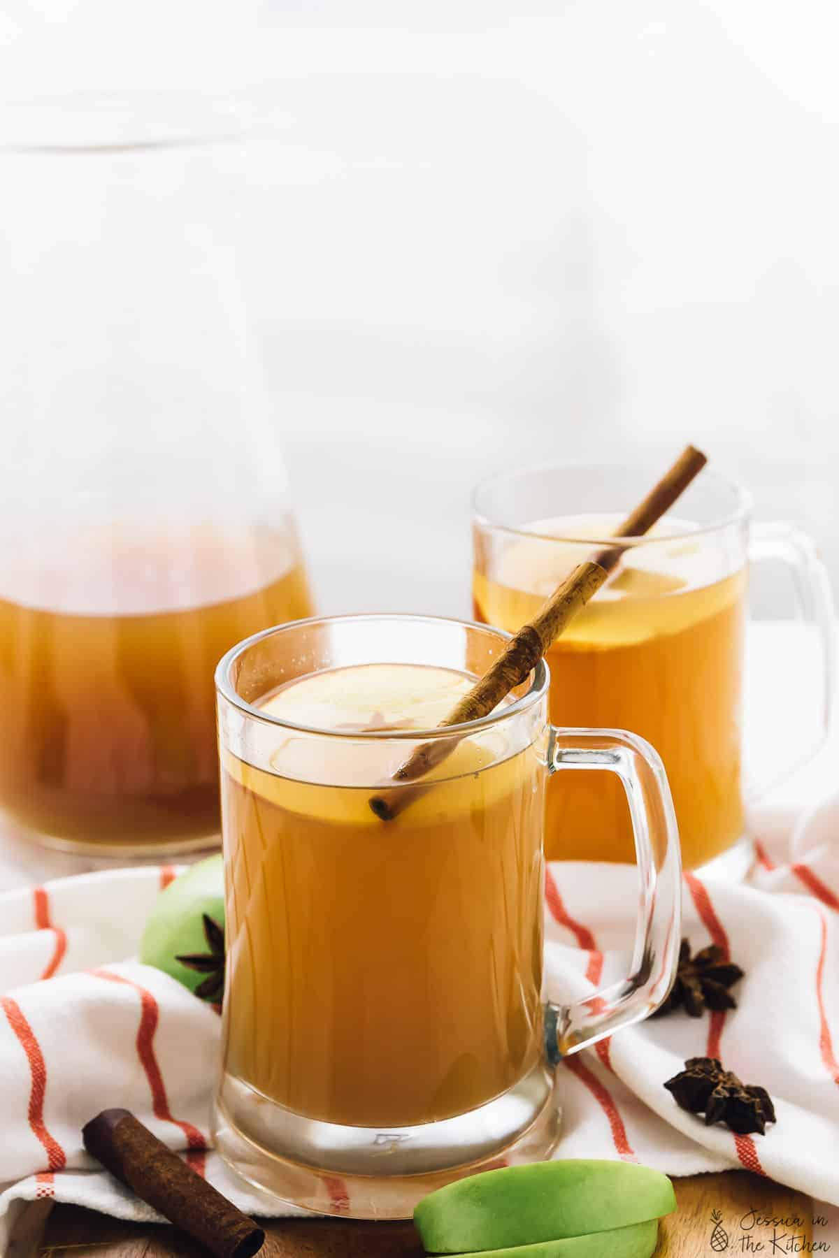 Two glass mugs of warm spiced apple cider with a cinnamon stick in one mug.