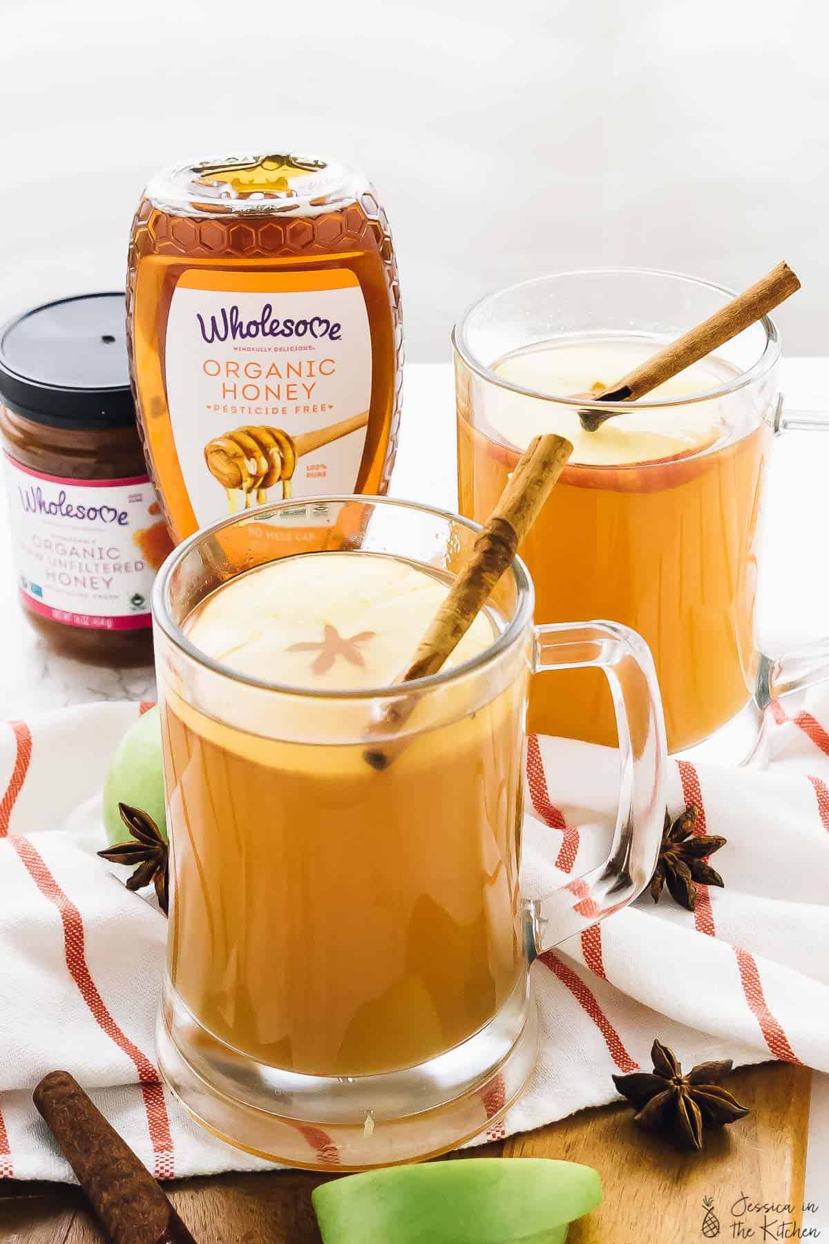 Warm spiced apple cider in two glass mugs with honey in the background.