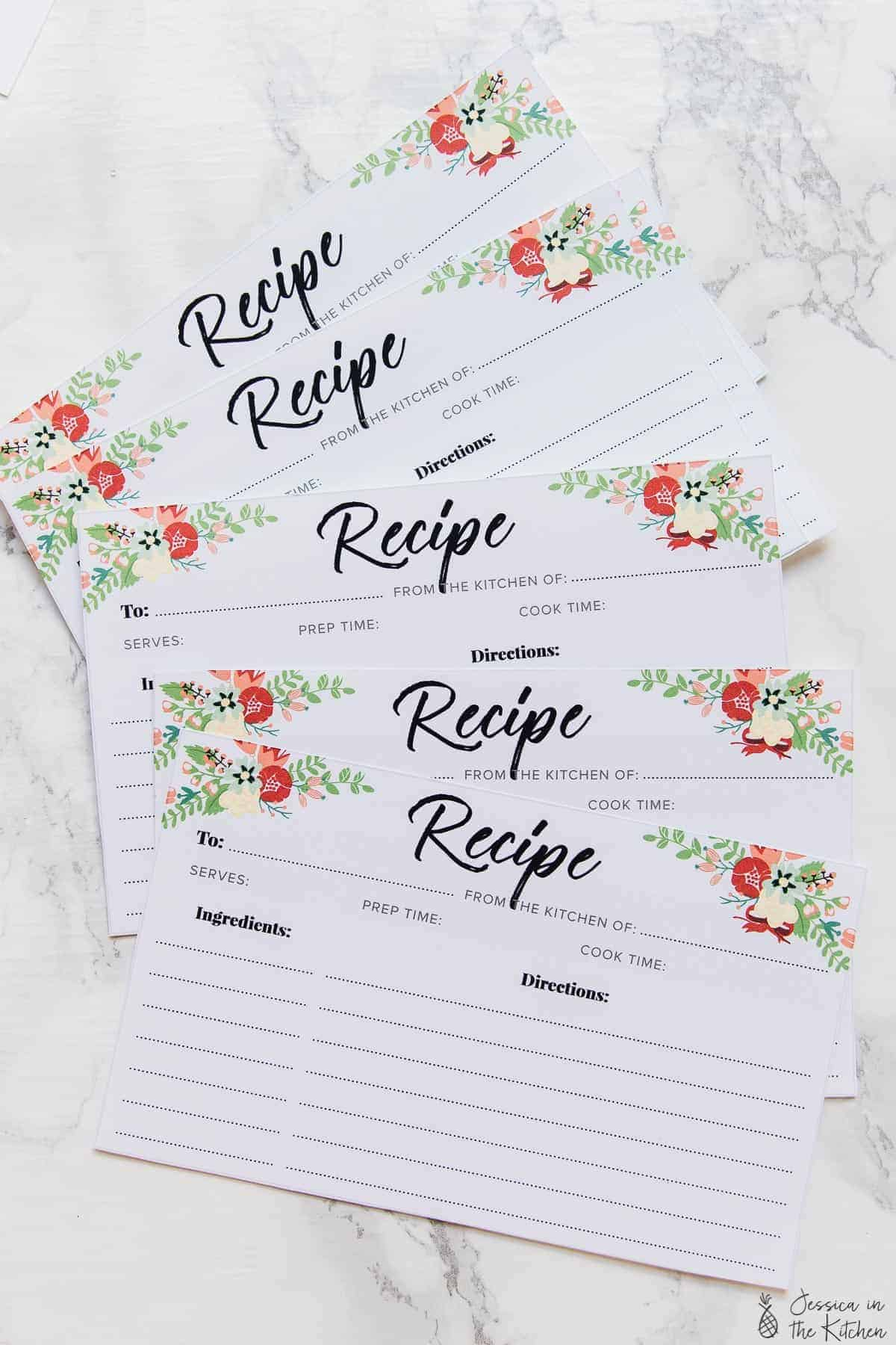 A bunch of printed recipe cards fanned out on a white table.