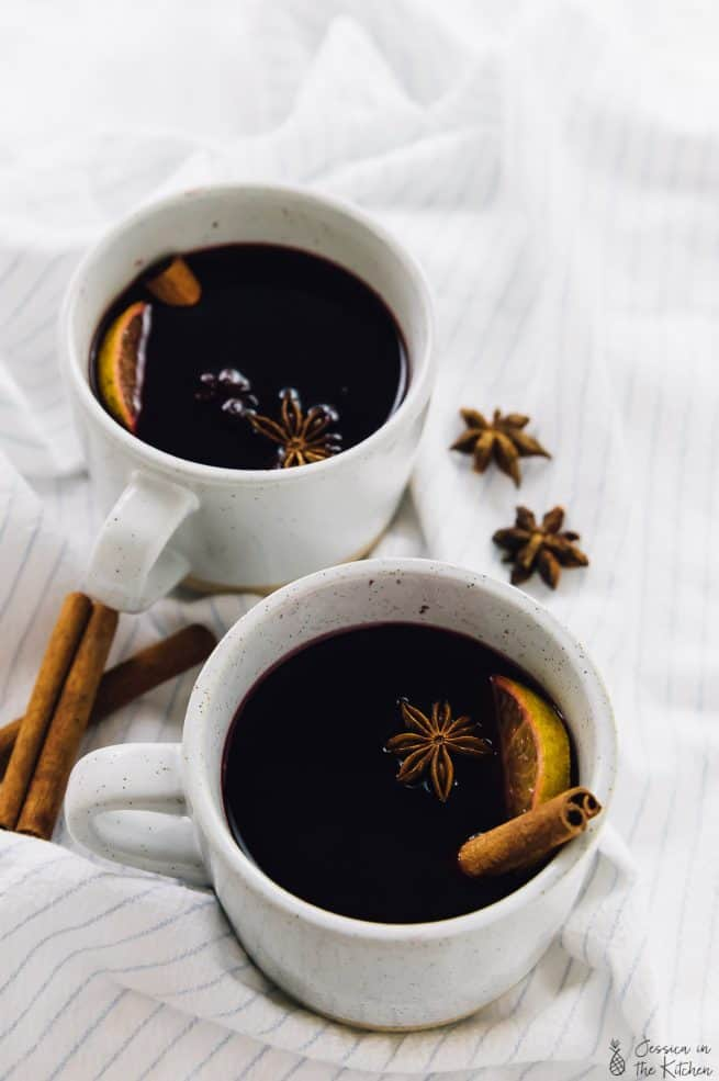 Two mugs of mulled wine on a striped cloth.