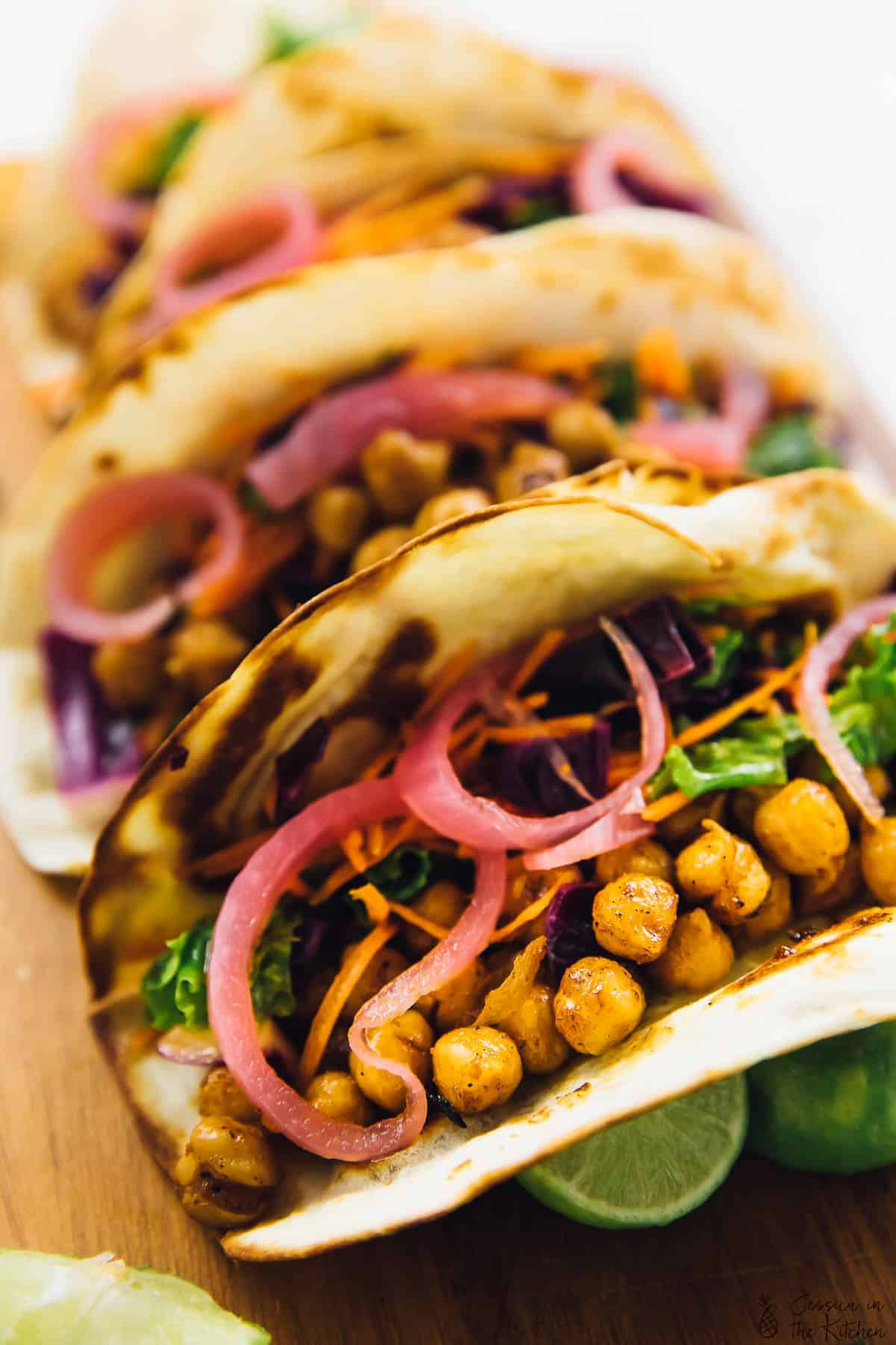 Close up of chickpea tacos on a wood board.