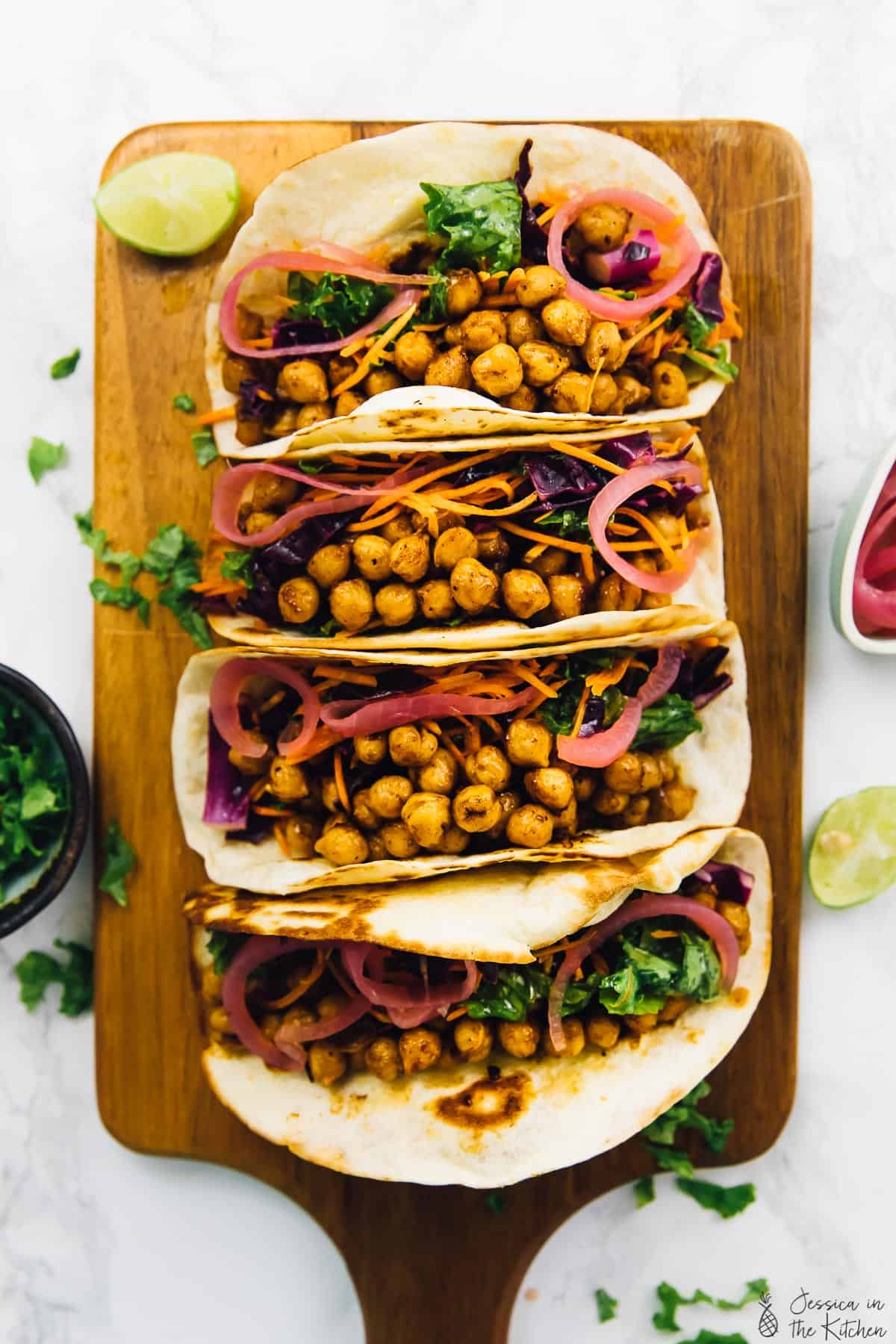 Overhead shot of bbq chickpea tacos on a wooden board with lime wedges on the side.