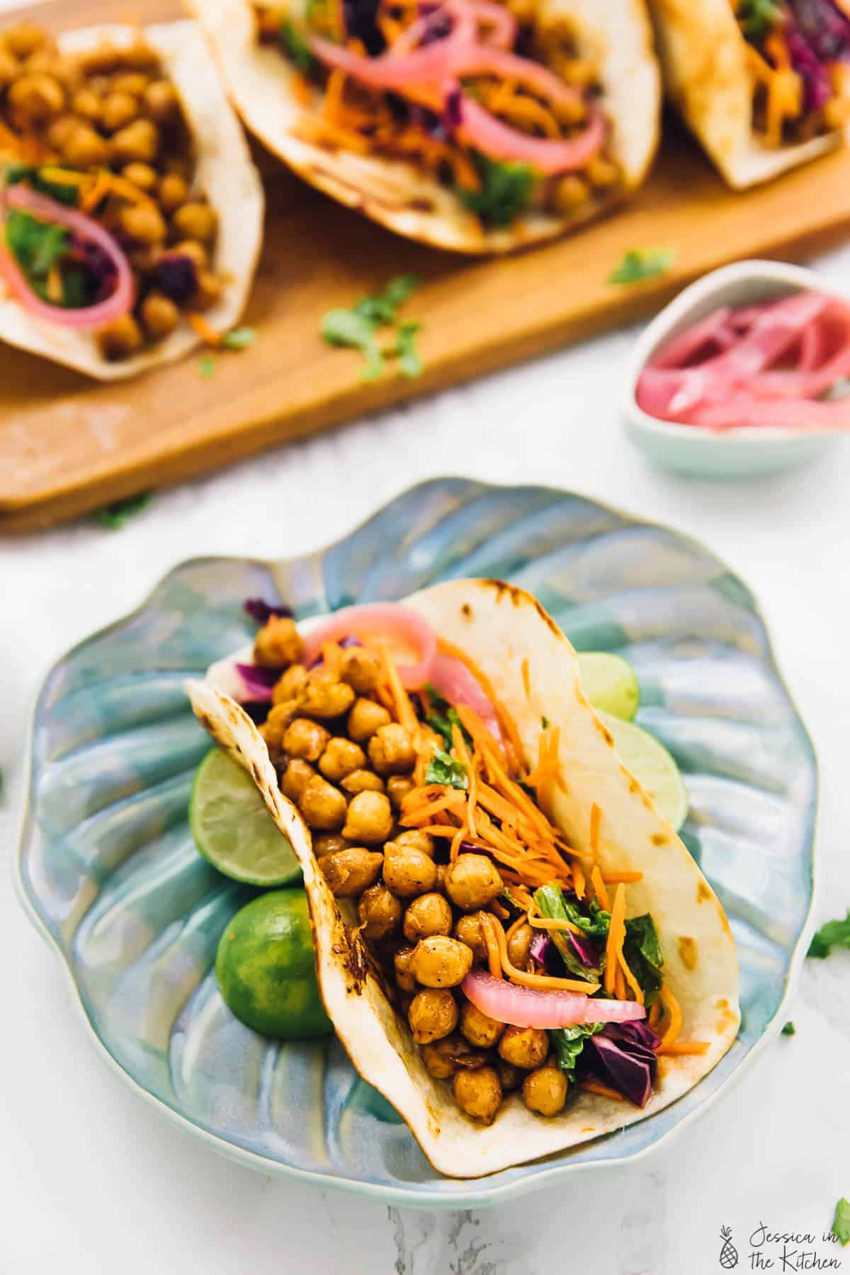 A chickpea taco on a blue plate with more tacos in the background.