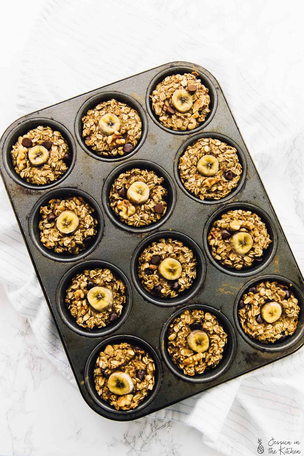 Overhead view of baked banana bread oatmeal cups in a muffin mold.