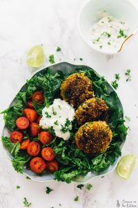 Top down shot of crispy quinoa patties on a bed of greens.
