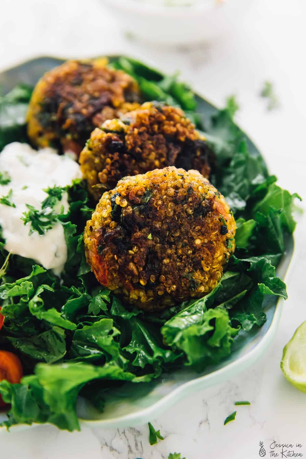 Close up of quinoa patties on a bed of greens.