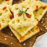 Focaccia bread squares on a wooden board.