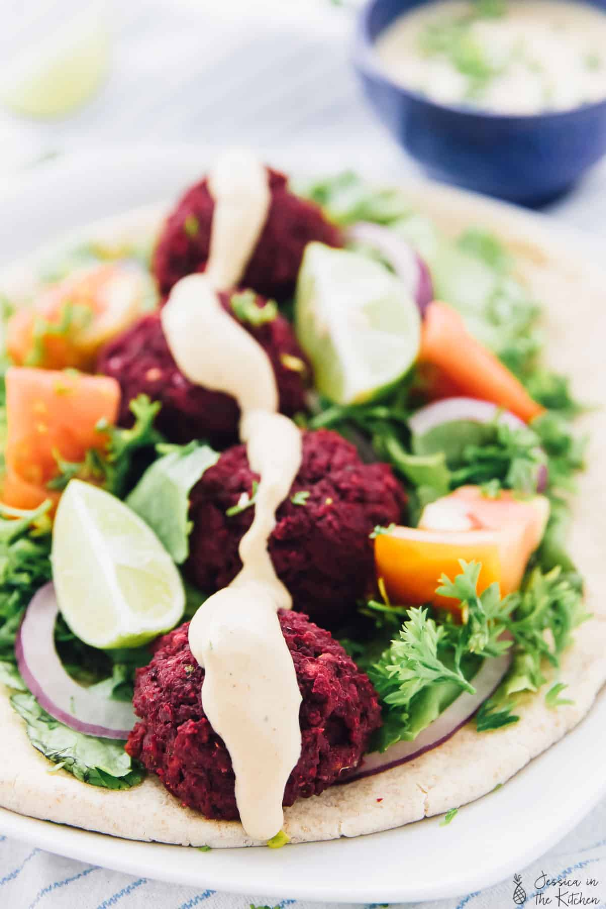 This Vegan Beet Falafel with Harissa Tahini Dressing is a beautiful colour twist on your traditional favourite falafel! It's baked instead of fried and tastes absolutely delicious!! via https://jessicainthekitchen.com