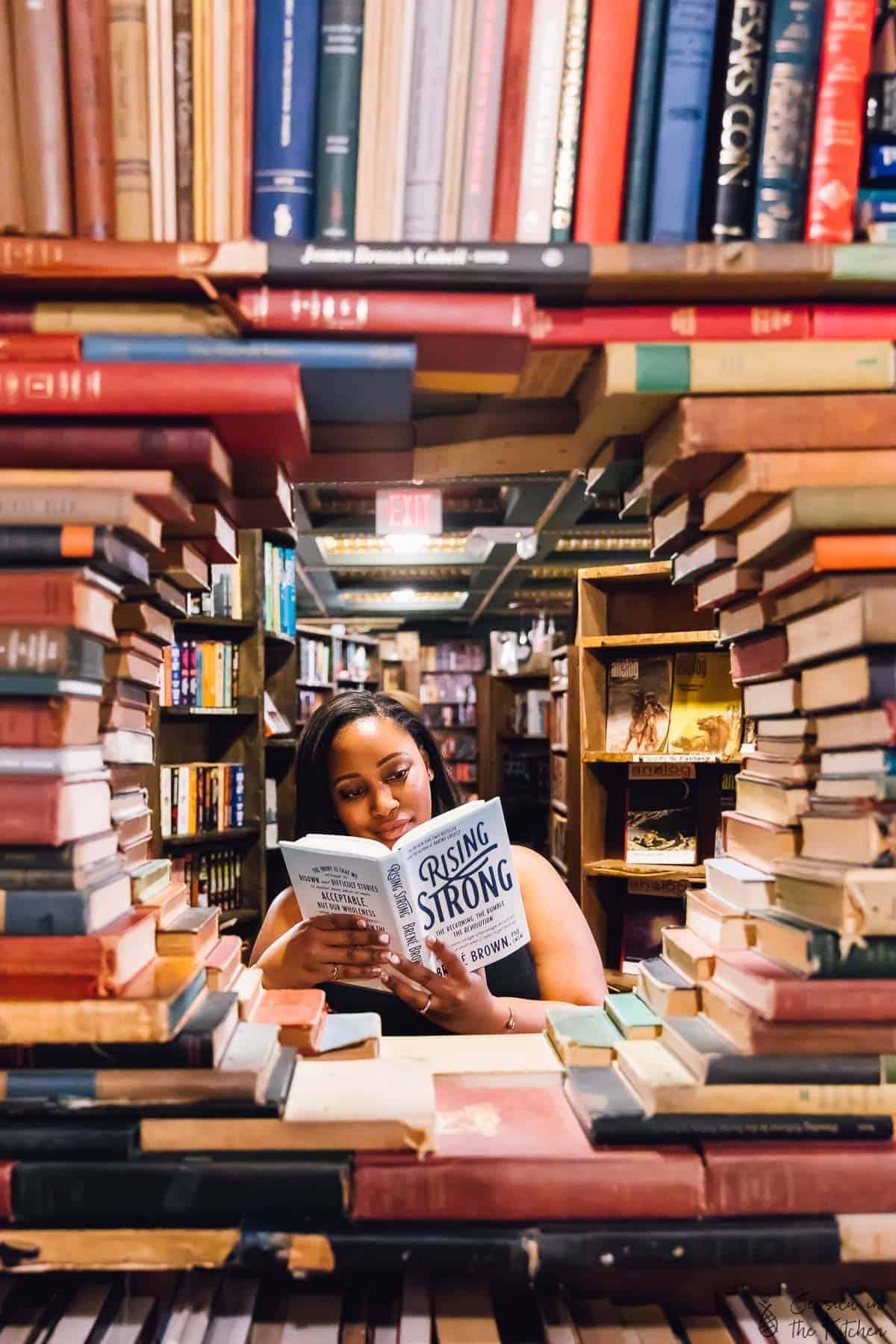 Jessica reading a book in a bookstore.