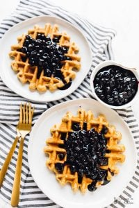 Overhead shot of lemon poppyseed waffles covered with blueberry sauce.