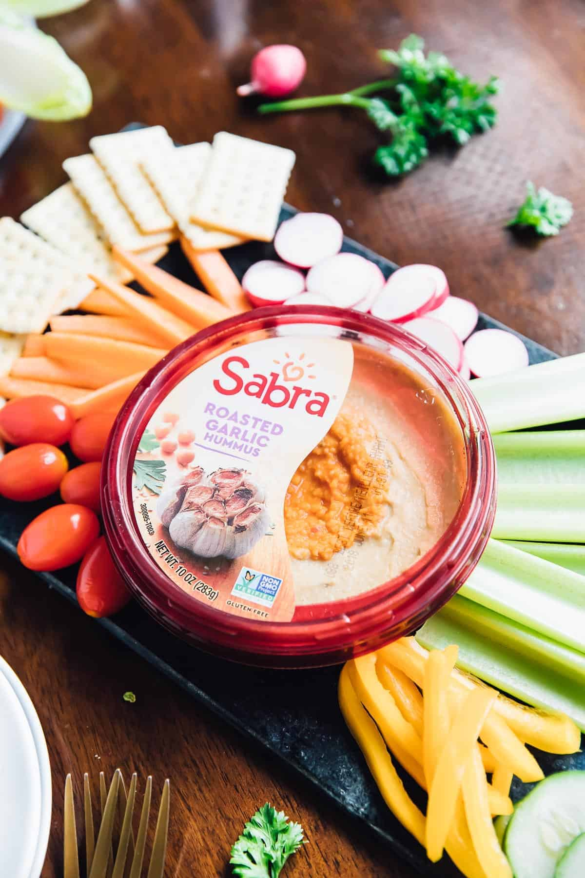 A tub of roasted garlic hummus, surrounded by raw vegetables.