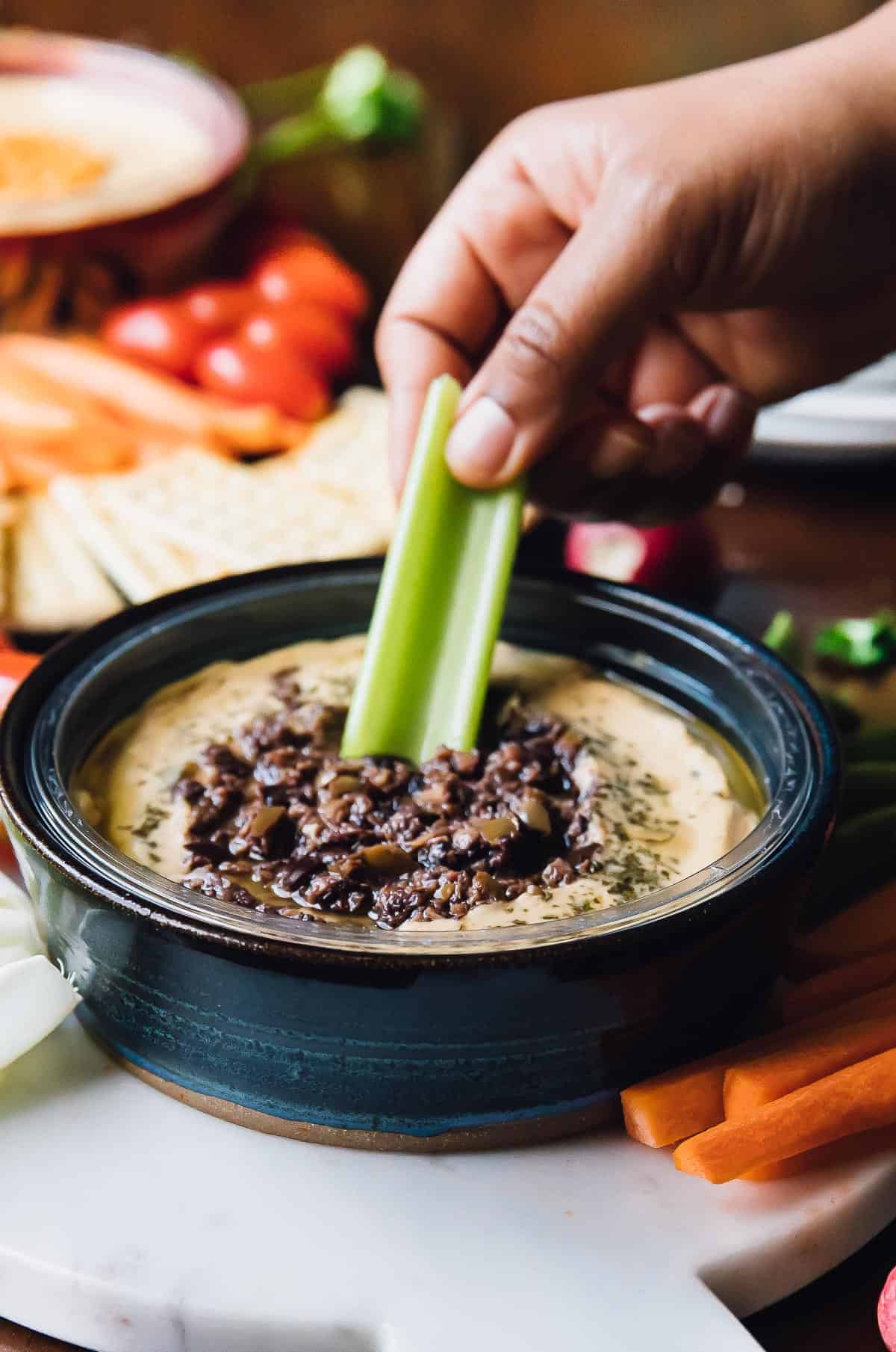 Hand dunking a celery stick into a blue bowl of dip.