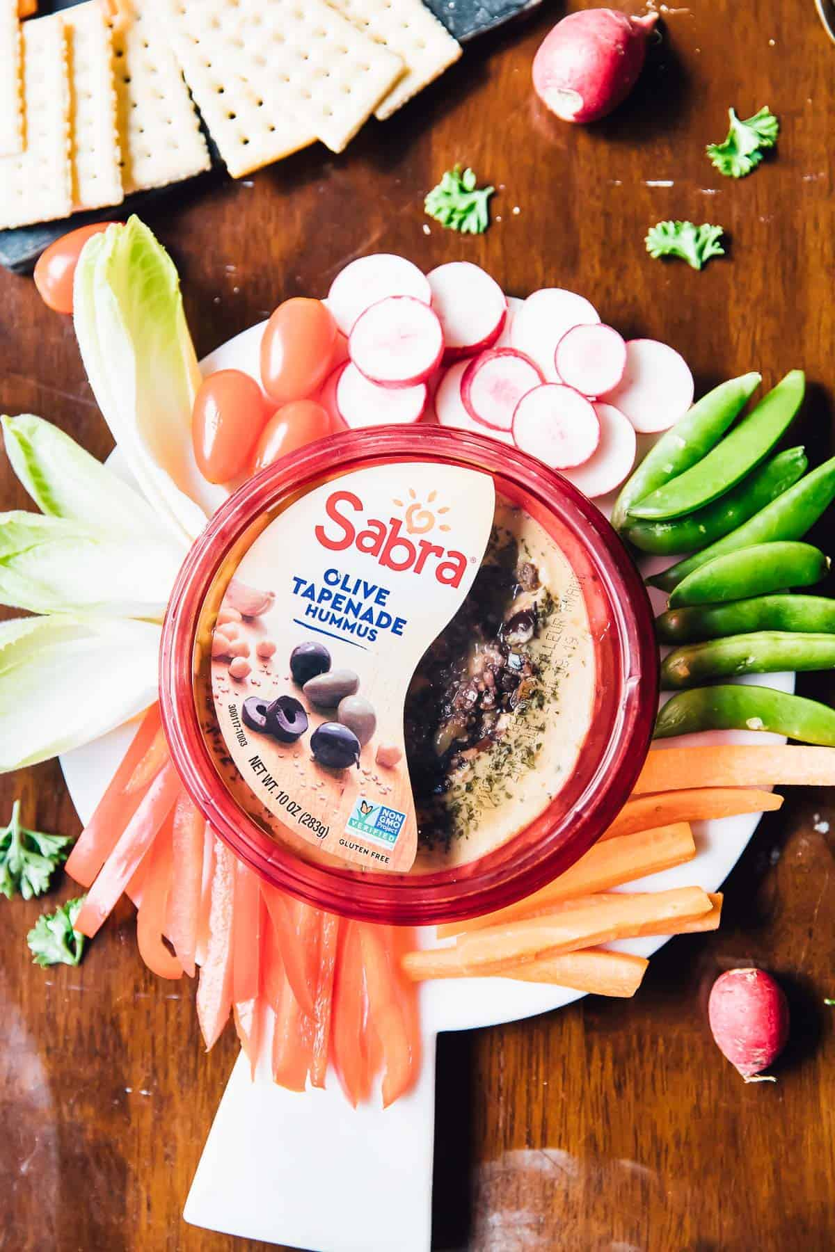 Top down shot of dip surrounded by raw vegetables.