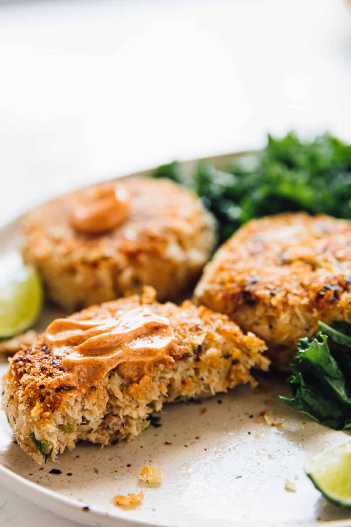 Vegan crab cakes, topped with sauce on a plate with salad on the side.