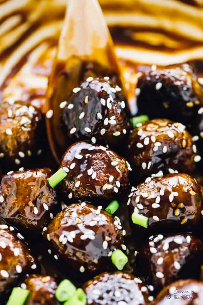 A spoon stirring vegan teriyaki meatballs.