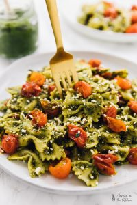 a fork being dug into pesto pasta on a plate with burst cherry tomatoes on top of the pasta