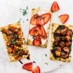 Three crisp bread summer appetizers on a white plate.