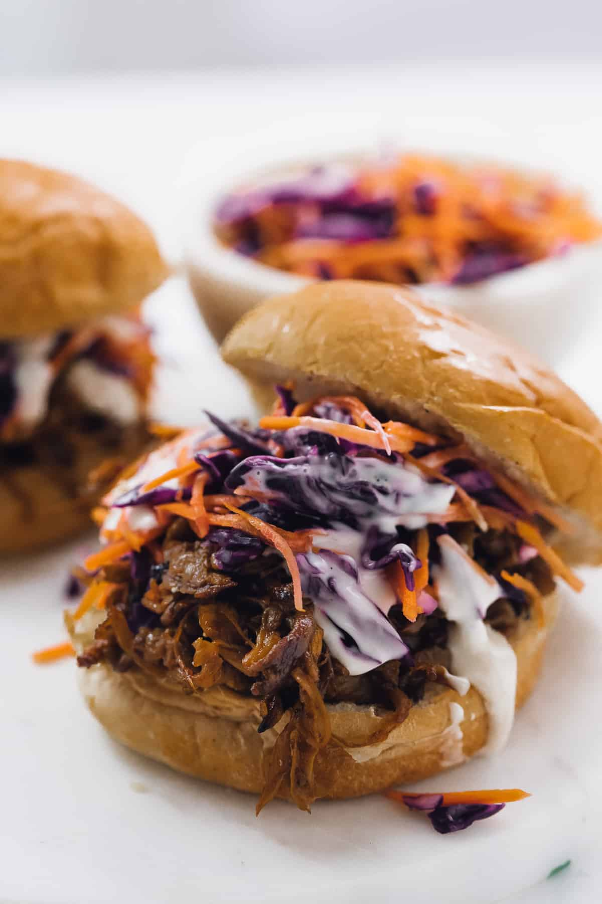A close up of a vegan pulled mushroom sandwich with sauce and slaw..