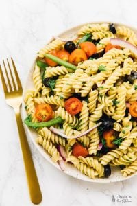 This 15 Minute Vegan Pasta Salad is perfect for lunch, a quick weeknight dinner, and so much more! It's loaded with flavour and topped with a flavourful homemade Italian vinaigrette! via https://jessicainthekitchen.com #veganrecipes #vegans #vegetarians #recipes #plantbased #veganmeal #meals #healthy #sauce #jamaica #veganlife #veganeating