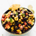 Black bean avocado and corn salad in a white bowl with a chip dipped in it.
