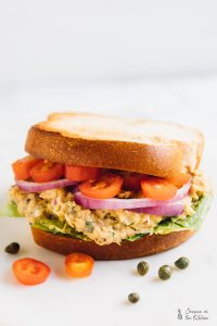 Side on shot of vegan tuna sandwhich with tomatoes and onions.