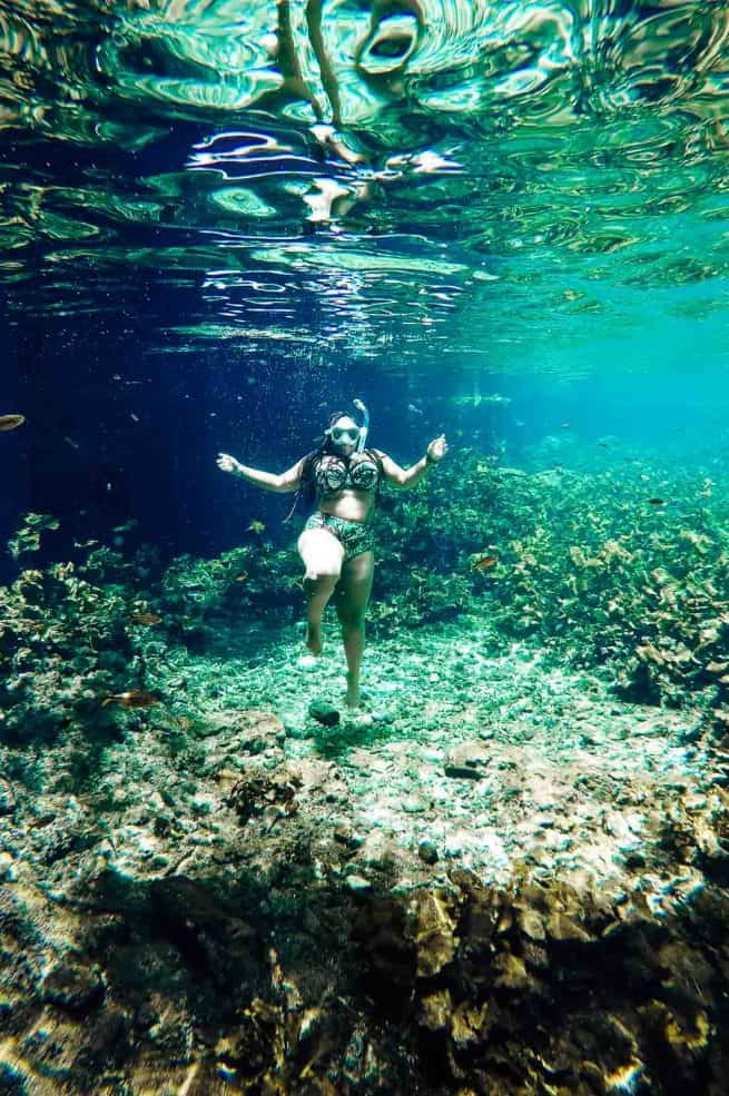Jessica underwater, wearing a snorkel.