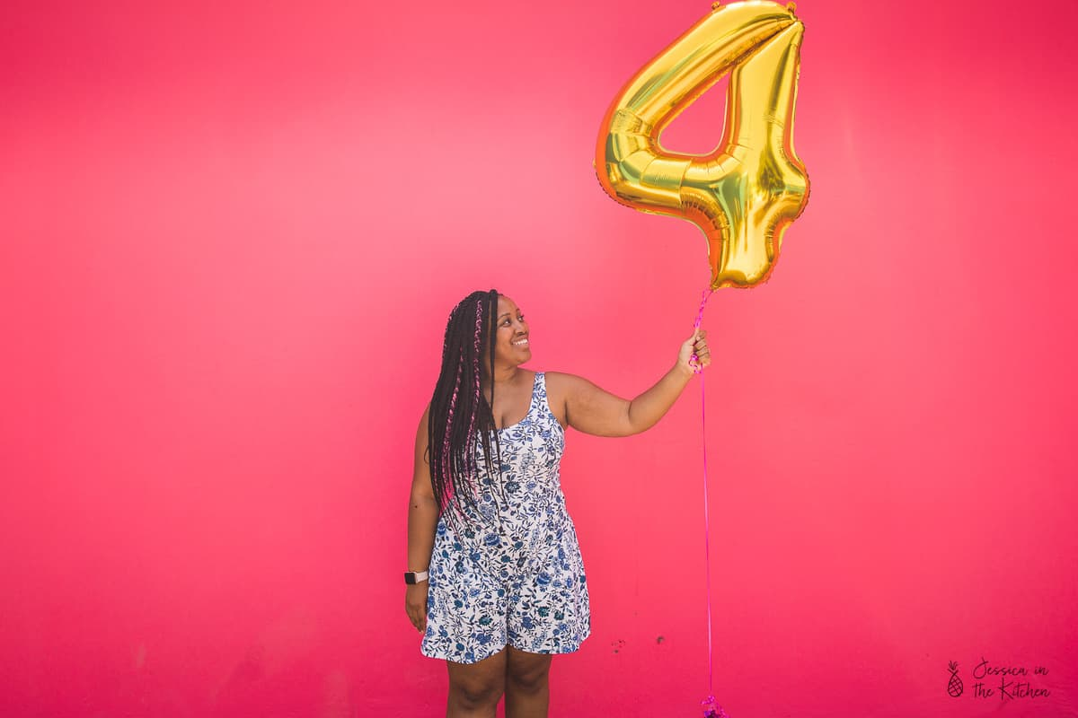 Jessica holding up a number four balloon.
