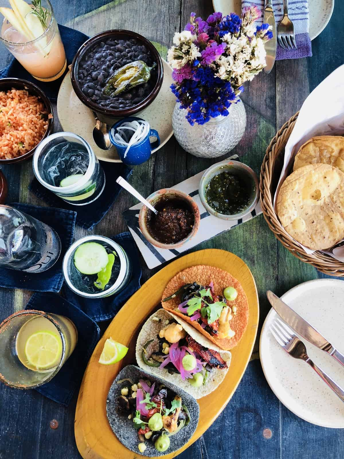 Top down view of drinks, sauces and tacos on a table.