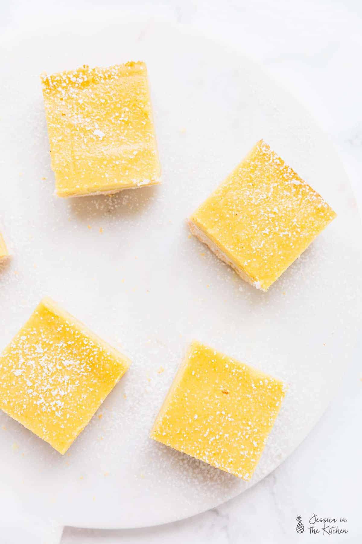 Overhead shot of vegan lemon bars on a white board.