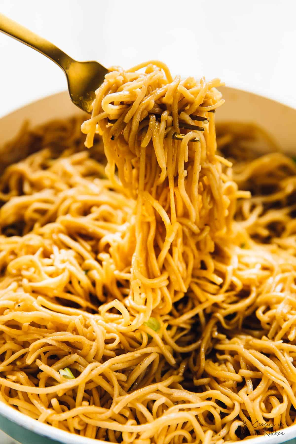 A fork holding up sesame noodles, over a bowl of noodles.