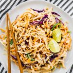 Asian noodle salad on a plate with chopsticks on the side.