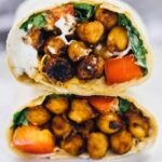 A bbq chickpea wrap cut on half on a plate.