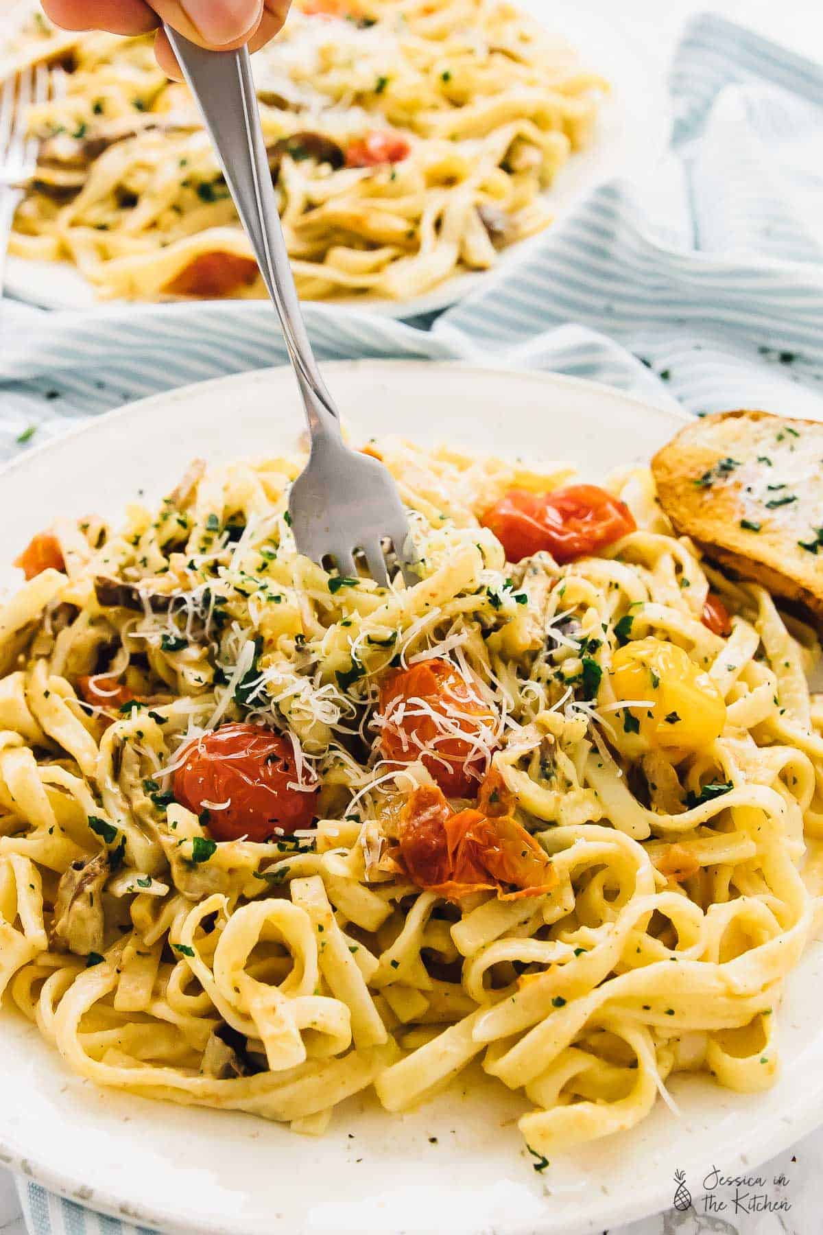 A fork in a plate of fettuccine pasta with burst tomatoes, fresh herbs, and Parmesan cheese