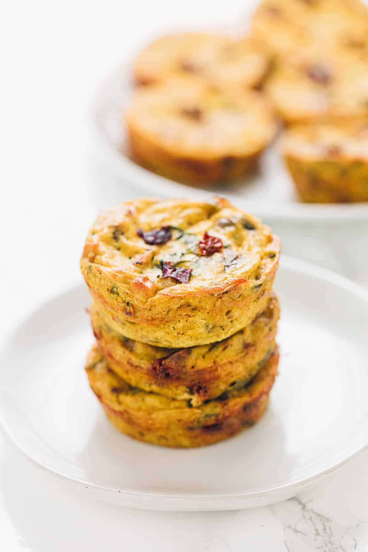 3 vegan quiche muffins stacked on a white plate