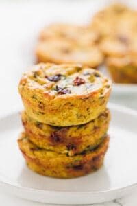 3 vegan quiche muffins stacked on a white plate close up
