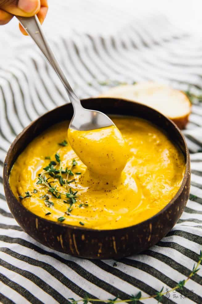 A spoon being dipped into a bowl of roasted sweet potato soup.