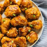 Overhead view of sweet and sticky orange cauliflower bites on a grey plate.